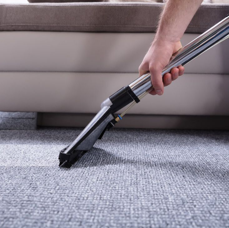 Worker steam cleaning carpet